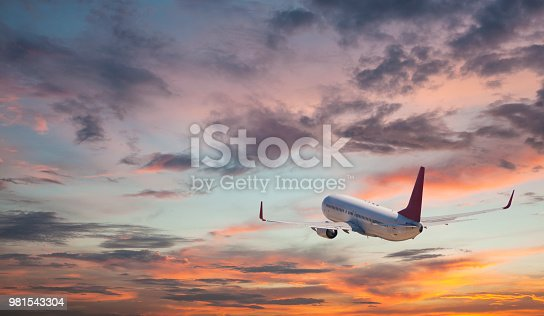 155439315istockphoto Commercial jet flying at sunset sky 981543304