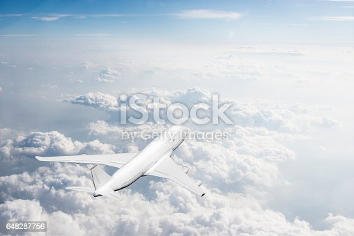 155380716 istock photo Commercial jet flying over clouds - 648287756