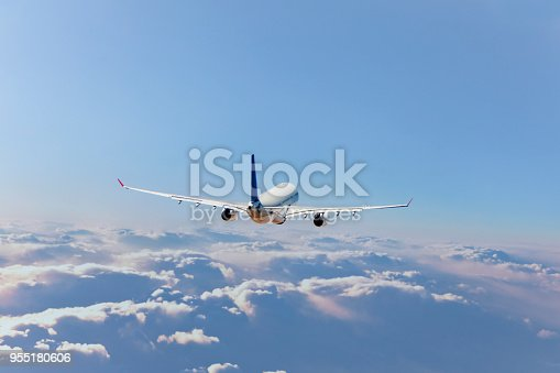 155380716 istock photo Commercial jet flying over clouds 955180606