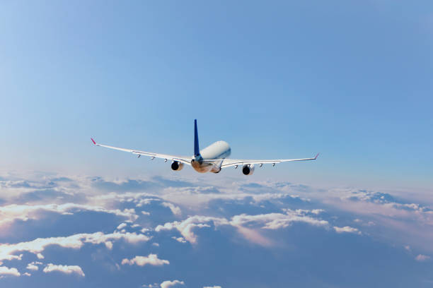 Commercial jet flying over clouds stock photo