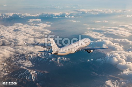 155380716 istock photo Commercial jet flying over clouds 962122806
