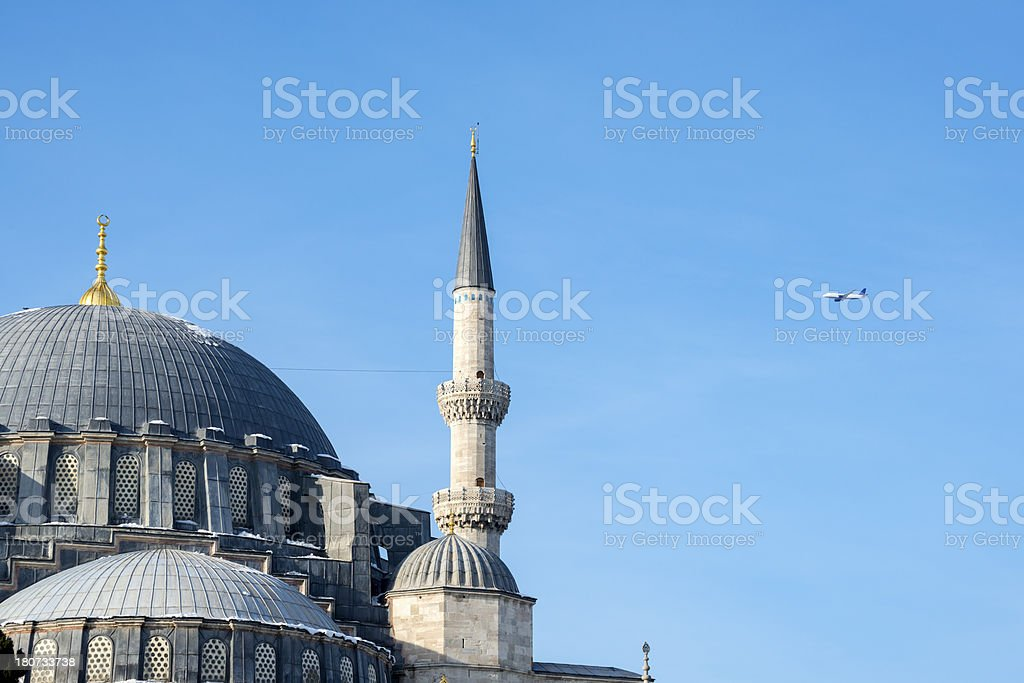 Commercial jet flying past Süleymaniye Mosque in Istanbul royalty-free stock photo