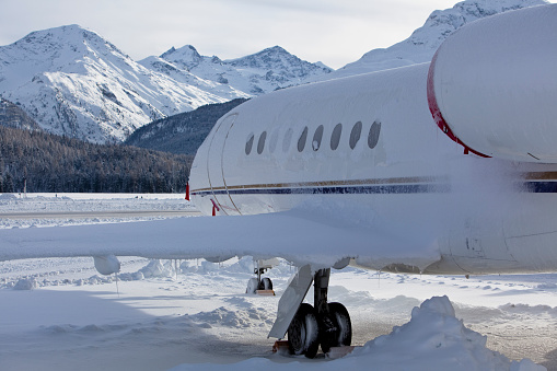 Commercial jet parked on the snow in the mountains.
