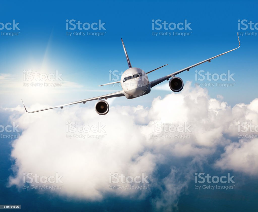 Commercial jet plane flying above clouds stock photo