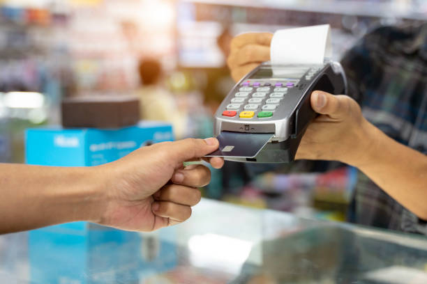 Commercial shopping ideas concept with cashier swipe credit card with card reader machine Commercial shopping ideas concept with cashier swipe credit card with card reader machine credit card purchase stock pictures, royalty-free photos & images