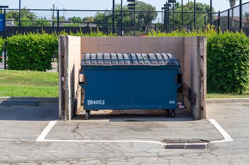 La Habra, CA, USA – July 12, 2021: A commercial trash bin with locked lid in a city park in La Habra, California.