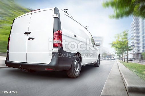 Rear view of a white commercial van driving in a city. Motion blurred city background with buildings and trees.