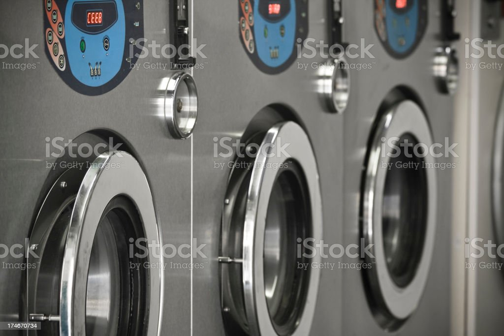 Commercial washing machines stacked on in a Laundromat stock photo