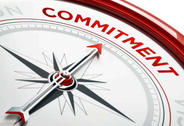 Commitment Concept: Arrow of A Compass Pointing Commitment Text Arrow of a compass is pointing commitment text on the compass. Arrow , commitment text and the frame of compass are metallic red in color. White background. Horizontal composition with copy space. Commitment concept. dedicated stock pictures, royalty-free photos & images