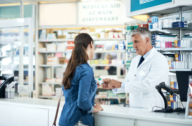 committed to keeping his customers healthy and happy - chemist stock photos and pictures
