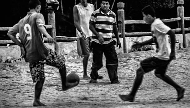 common people playing football. Street scene in Ilhabela, Brazil/ Footbal2014 stock photo