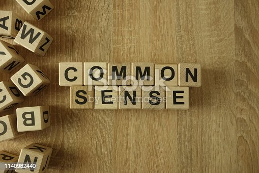 Common sense text from wooden blocks on desk