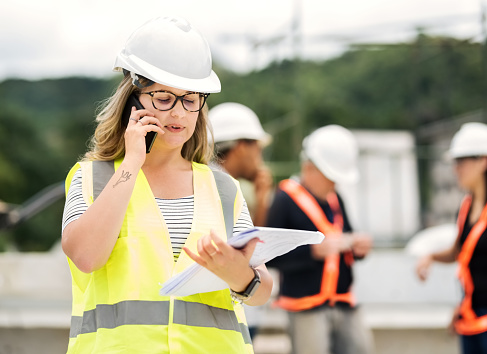 Shot of a female engineer working at construction site making a phone call with coworkers in background