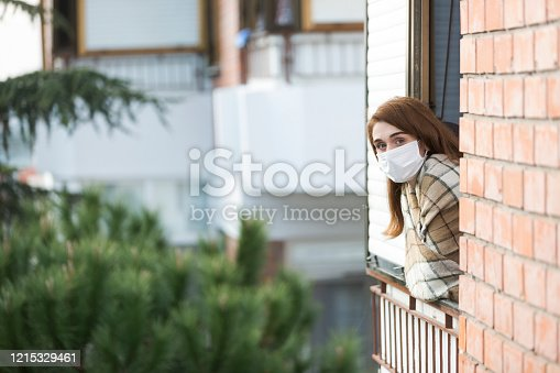 Young woman communicating with neighbor during pandemic with her protective mask.