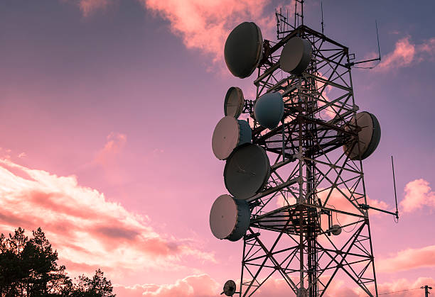 Communication and transmission tower for military use Communication and transmission tower for military use over a magenta sky telecommunications equipment stock pictures, royalty-free photos & images