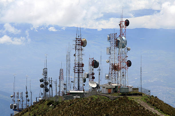 Communication Antennas Photo of several communication antennas and tours in Quito, Ecuador. The communication antennas are located on the top of a mountain summit. The sky is very clouded and it is a grey day. There is a mountain range in the foggy background.  antenna aerial stock pictures, royalty-free photos & images