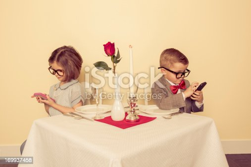 A young boy and girl are on a date, and really would rather play with their mobile devices than be with each other.