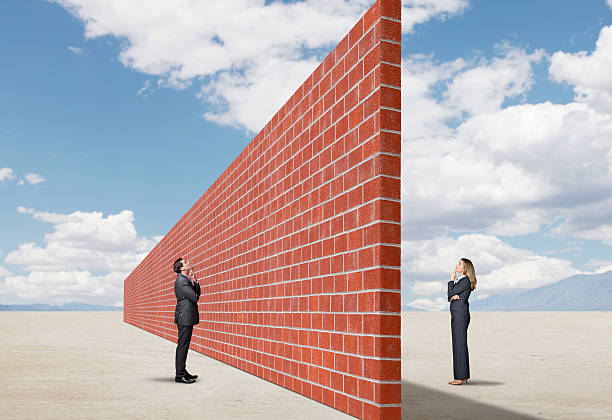 Communication Problem A businessman and a businesswoman stand on opposite sides of a tall and long brick wall that stands in an open and remote desert scene.  They are both wondering how they will overcome the barrier in communication represented by the wall. boundary stock pictures, royalty-free photos & images