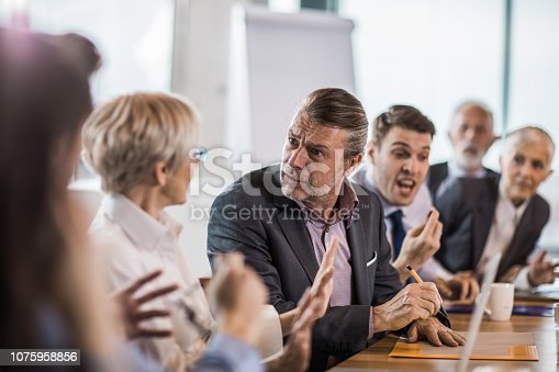 Frustrated businessman arguing with his colleagues during a business meeting in the office.