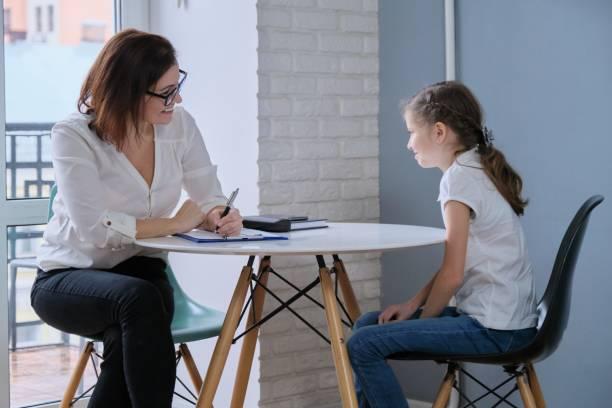 Okul psikoloğu ve kız 9, 10 yıl iletişim oturumu stok fotoğrafı