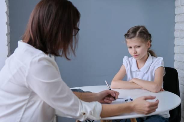 Sesión de comunicación de la psicóloga escolar y niña - foto de stock