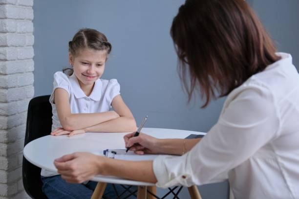 Okul psikoloğu ve kız çocuğun iletişim oturumu stok fotoğrafı