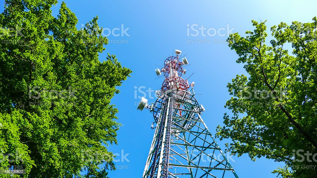 Communications tower in the sun against a blue sky stock photo