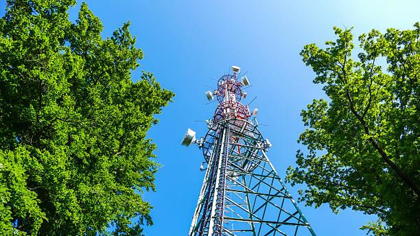 torre di comunicazione di sole contro un cielo blu - ripetitore foto e immagini stock