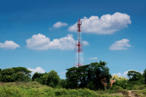 communications tower on field with cloudy sky - emissione radio televisiva foto e immagini stock