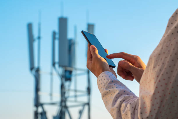 5G communications tower with man using mobile phone stock photo