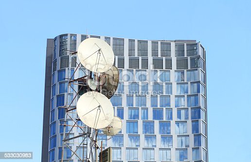 istock Communications tower with modern building in background 533030983