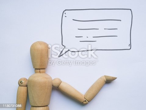 Wooden figure doll with speech bubble.