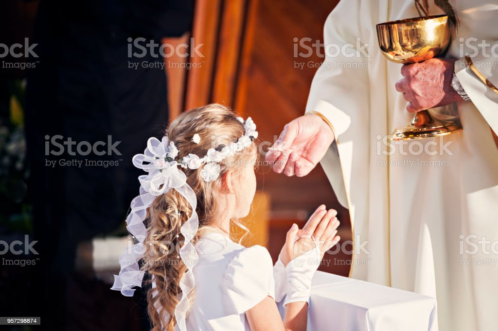 Communion and clergyman. First Holy Communion stock photo