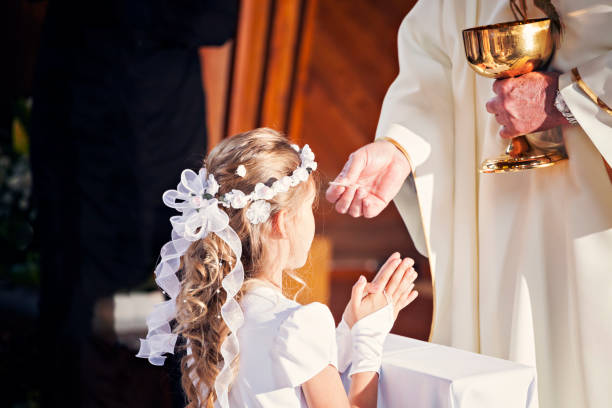 communion and clergyman. first holy communion - communion stock photos and pictures