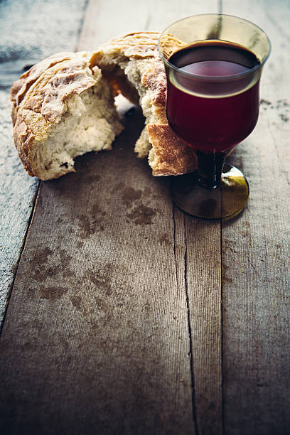 communion bread, wine, and grapes on black background - communion stock photos and pictures