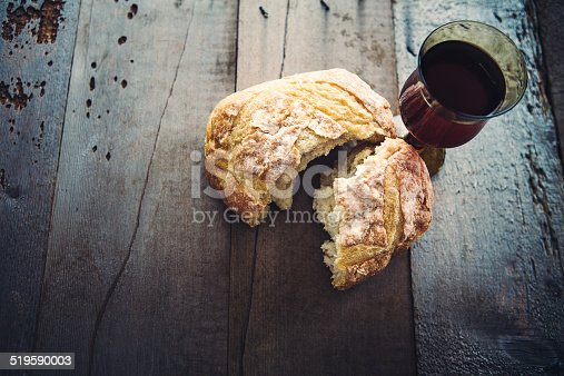 A rustic high contrast still life of bread and wine, representing the Last Supper of Jesus Christ, his blood and body.  The elements rest on a weathered gray wood background.  Vertical with copy space.