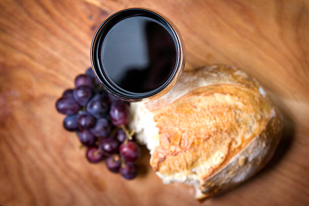 Communion Bread, Wine, and Grapes on Rustic Wood stock photo