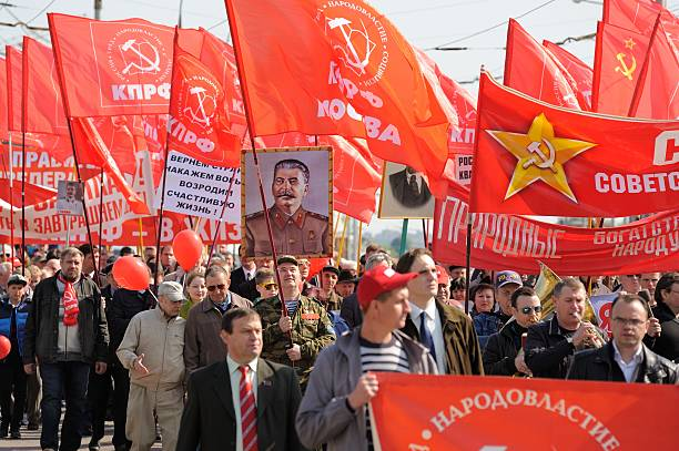 Parti communiste de démonstration. Personnes portant rouge drapeaux et le portrait de Staline - Photo
