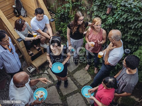 Diverse group of people having an outdoor party in the garden of urban home in North American city.