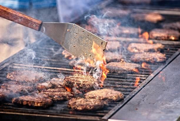 Community BBQ cooking hamburgers, smoke and flames. stock photo