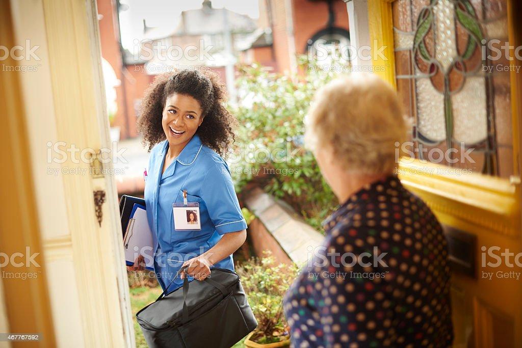 community care nurse visit to senior stock photo