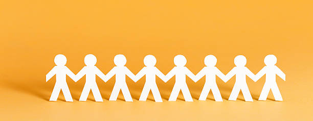 Community concept Paper people standing in a row holding hands. Banner format. people in a row stock pictures, royalty-free photos & images