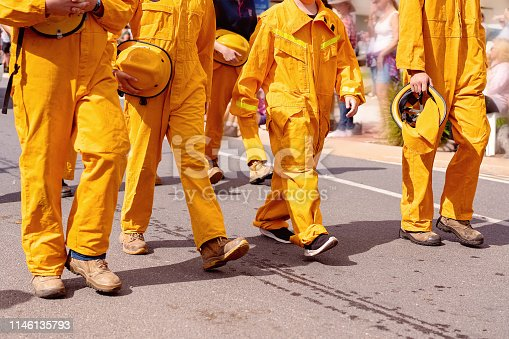 A team of community firemen emergency workers marching in a street parade during a festival