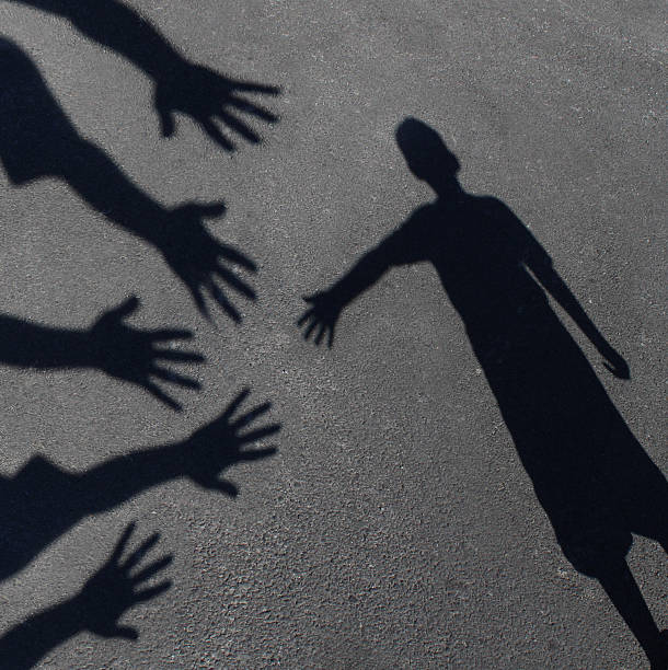 Community Support Community support and helping  children concept with shadows of a group of extended adult hands offering help or therapy to a child in need as an education symbol of social responsibility t for needy kids and teacher guidance to students who need extra care. social responsibility stock pictures, royalty-free photos & images