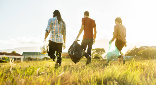Community volunteers walking through a field after a litter cleanup day stock photo