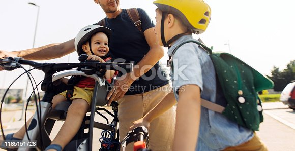 Boy commute to school with dad and baby brother by bicycle