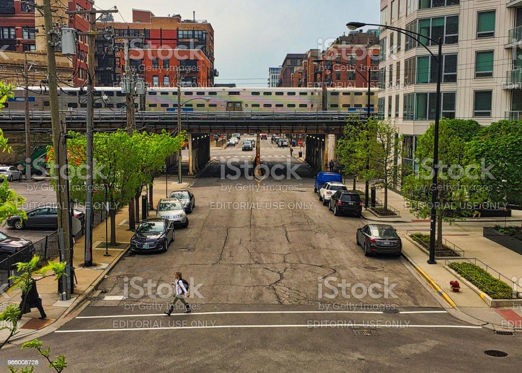 Pendler überquert Fulton Street, während Metra Zug erhöhte Strecke im Hintergrund durchquert - Lizenzfrei Blickwinkel-Aufnahme Stock-Foto