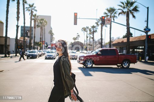 Young woman commuting in Los Angeles, California on a nice sunny day. She is wearing casual clothing, an olive colored jacket and sunglasses.