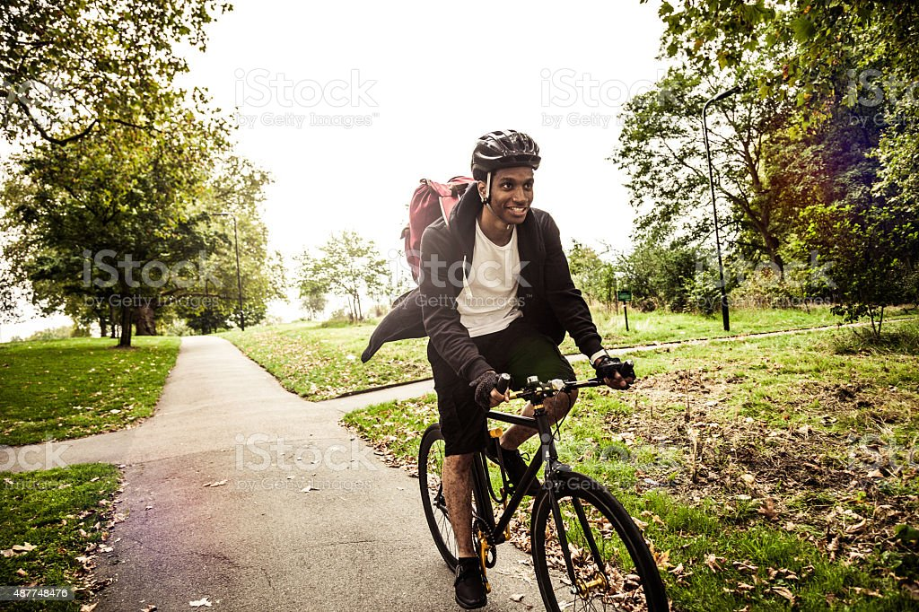 Commuter cycling in the park going at work in London stock photo