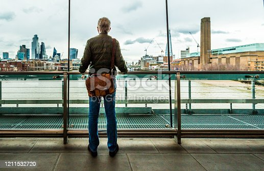 Wide angle color image depicting a rear view of a male commuter in his 50s or 60s looking through the window at a railway station in central London, overlooking the modern city skyline and river Thames. The man wears casual denim jeans, a green down jacket and a brown leather messenger bag.